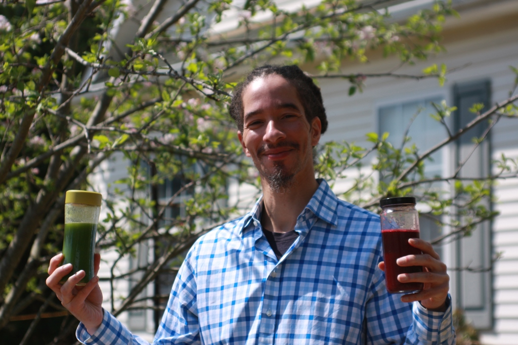 Local Chef Terrance Murphy from Meallennial Living stands under an apple tree in my front yard permaculture food garden holding 2 bottles of raw vegetable juice - Beet Breeze and Tri-Greens.